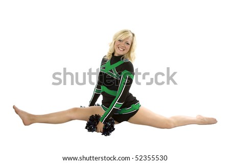 A cheerleader in the splits with her pom poms down.  She is wearing a green and black outfit. - stock photo