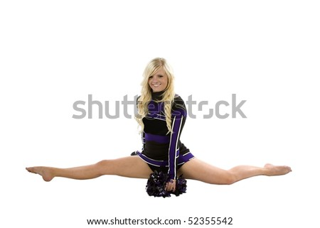 A cheerleader is doing the splits with her pom poms down on the ground.  She is smiling - stock photo
