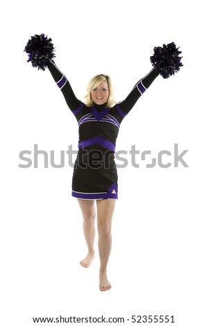 A cheerleader is standing with her pom poms up in the air.