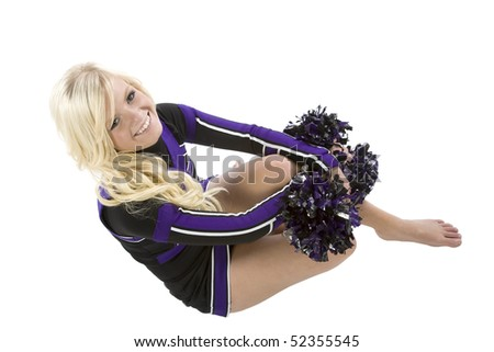A cheerleader sitting on the ground with her pom poms looking up. - stock photo