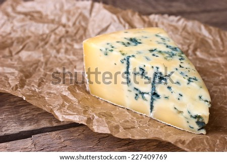 A cheese with a blue mold on the paper on the wooden background