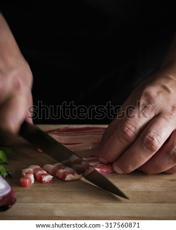 A Chef Cutting Bacon (Pancetta). Shallow Depth of Field. Motion Blur.