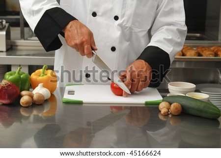 A chef cutting fresh vegetables in a restaurant kitchen. - stock photo