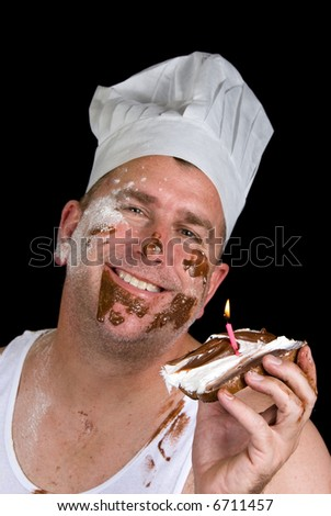 A chef examines his gourmet birthday creation consisting of burnt toast, chocolate and vanilla icing and a candle. - stock photo