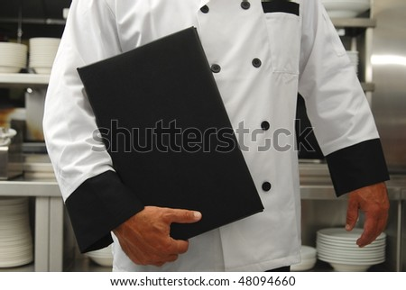 A chef holds a menu in a restaurant kitchen - stock photo