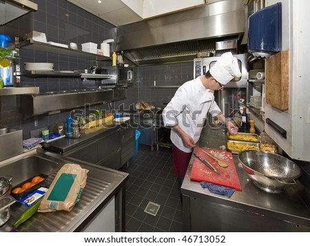 A chef in a professional kitchen, preparing dinner - stock photo