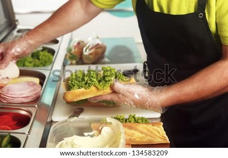 A chef preparing a sandwich with fresh salad - stock photo