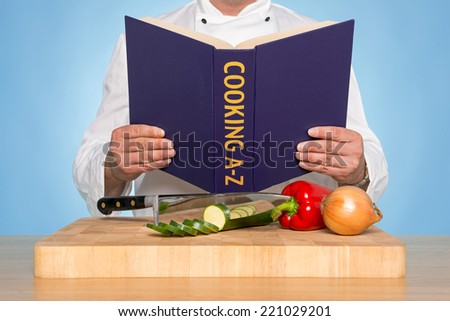 A chef reading a COOKING A-Z book - stock photo