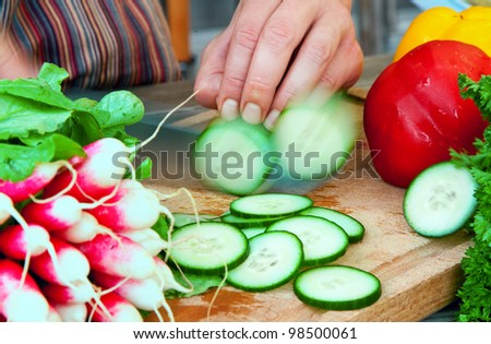 A chef's hands preparing a salad by chopping cucumber with raddishes and pepper - stock photo