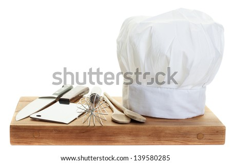 A chef's toque with various cooking utensils - stock photo