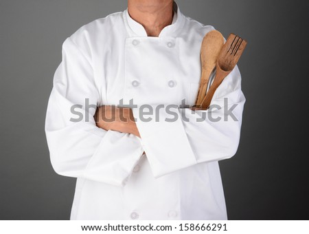A chef with his arms folded holding wood utensils. Man is unrecognizable. Horizontal format on a light to dark gray background. - stock photo