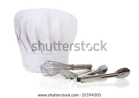 A chefs' kitchen tools including spoons, wisk, tongs and a toque or hat on a white background with copy space - stock photo