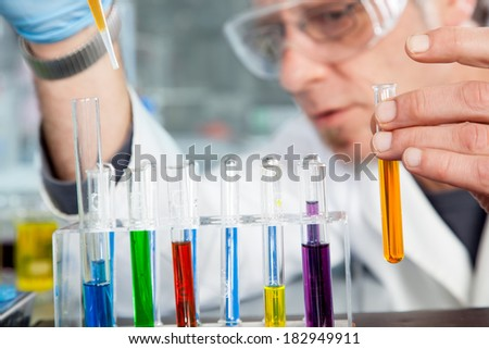 A Chemist is using a pipette to refill a test tube. - stock photo