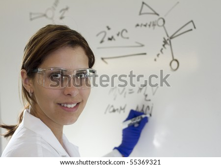 a chemist writing out equations on a white board for her students - stock photo