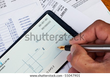 A cheque being signed, surrounded by bills - stock photo