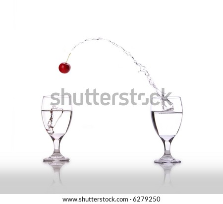 A cherry jumping from one glass to another. - stock photo