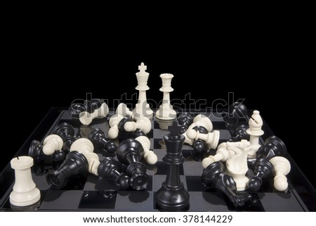 A chess board showing white pieces in checkmate and all pieces scattered. - stock photo