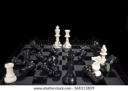 A chess board showing white pieces in checkmate and black pieces scattered. - stock photo