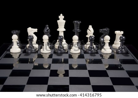 A chess board with black and white pieces together as a team - stock photo
