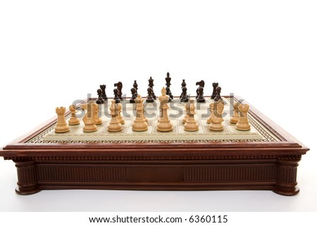 A chess gameboard with playing pieces ready. . Each player has 16 playing pieces and white always plays first.