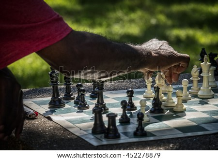 A chess player hesitates before making his next move. - stock photo