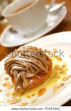 a chestnut cream cake with almond chips on a white plate with tea cup in the background - stock photo