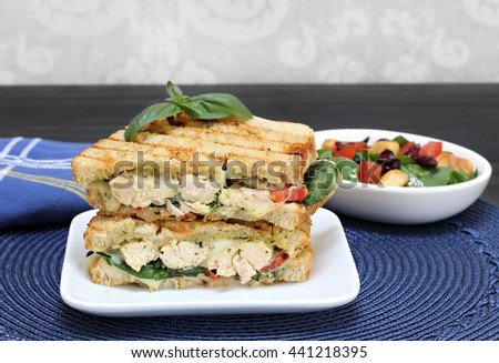 A chicken, cheese, pesto, basil, tomato, and spinach panini sandwich stacked on a white plate.  Macro image.