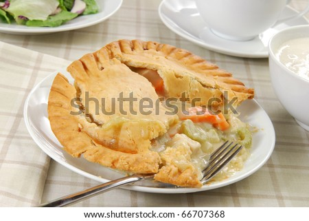 A chicken pot pie with a bowl of clam chowder and a green salad - stock photo