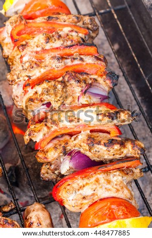 A chicken shawarma kebab skewer gently cooking on a barbecue - stock photo