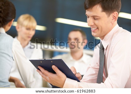 A chief manager signing a project and smiling against his three colleagues - stock photo