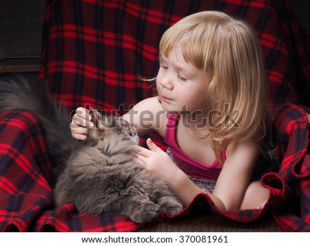 A child and a cat. Little girl sitting in a chair, a red plaid and curiously examines cat ears. The cat is suffering child's play. Girl blonde child 3 years - stock photo