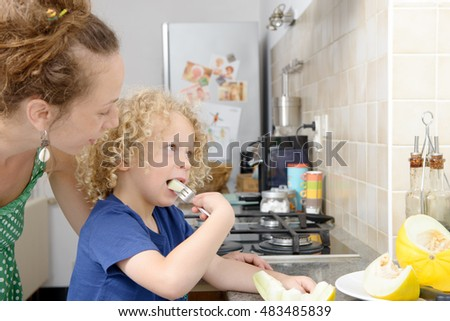 a child and his mom with a melon in kitchen