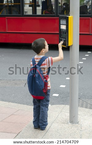 A child boy standing on a pavement or a side walk pushing the button on the traffic  signals for pedestrian crossing, road safety concept. - stock photo
