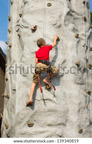 A child climbs a rock-climbing wall - Tower - stock photo