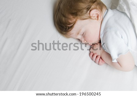 A child curled up on it's side sleeping. - stock photo