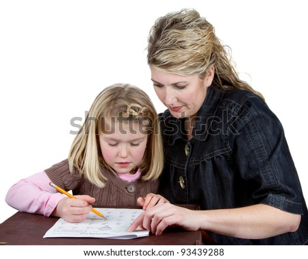 A child does her homework while her mother or teacher helps her, isolated on a white background - stock photo