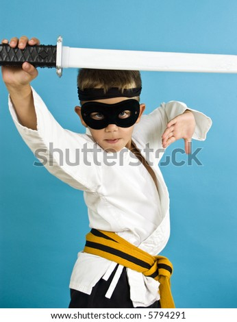 A child dressed in a makeshift costume for Halloween in an effort to look like a Ninja. - stock photo