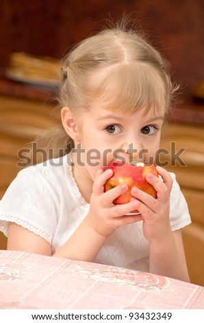 A child eats a juicy fresh apple. - stock photo