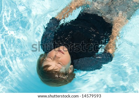 A child floats on his back in a fresh water swimming pool during a hot summer day. - stock photo