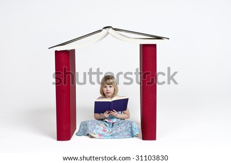A child girl reading a book in a house built of books - stock photo