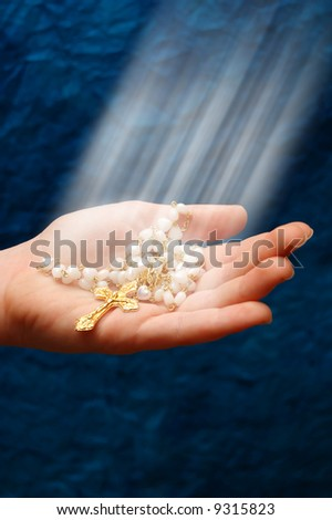 a child hand keeping a gold cross under rays of light - stock photo