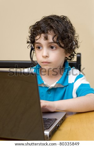 A child handles a computer as he does with a toy - stock photo