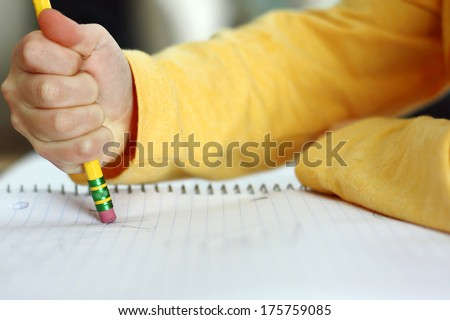 a child has made a mistake while writing and is holding a pencil and erasing on white notebook paper - stock photo