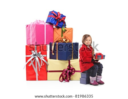 A child holding a gift next to a pile of gifts isolated on white background