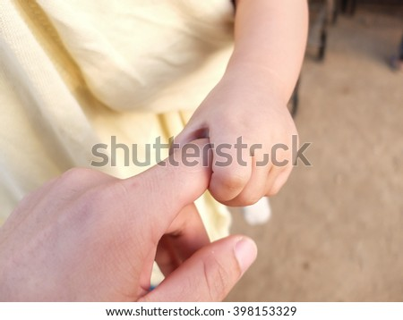 A child holding father's finger - stock photo