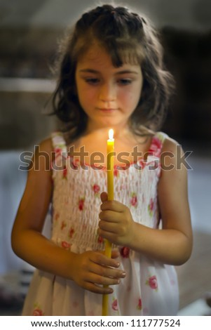 A child holds a candle in hands, focus on candle