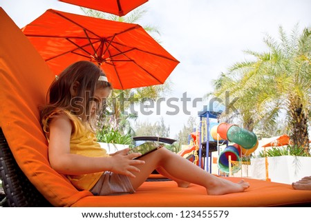 A child holds a tablet on a lounger on the beach under an umbrella - stock photo