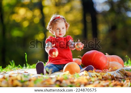 A child in a red dress plays in the open air, in his hands he holds A red apples. The kid sitting next to pumpkins and holding an apple in his hand. Thanksgiving day