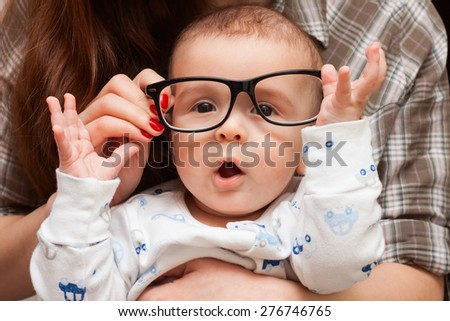 a child in her mother's glasses. funny baby in glasses - stock photo