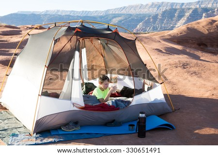 A child in the early morning in a tent on a stone plateau. Grand Staircase-Escalante National Monument, Utah - stock photo
